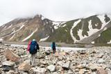Hikier is jumping on rocks in Caucasus mountains in Bezengi regi