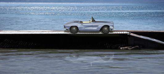 Klassischer Sportwagen auf einem Steg im Wasser