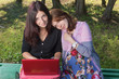 Two young women look a computer