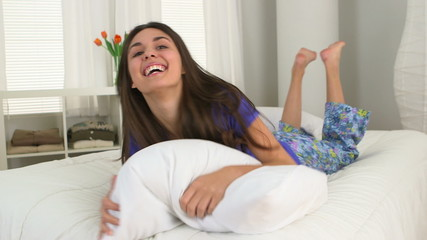 Playful young Caucasian woman lying on bed