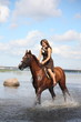 Beautiful teenage girl riding horse in the river