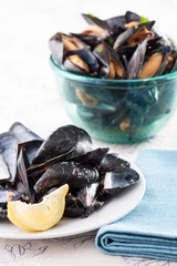 Dish of mussel shells and bowl of mussels