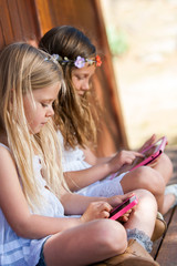 Kids playing with tablet and smart phone outdoors.