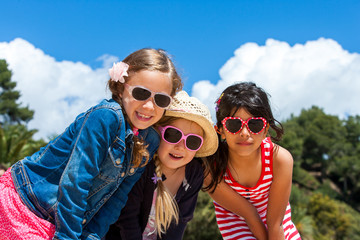 Three girls wearing sunglasses.