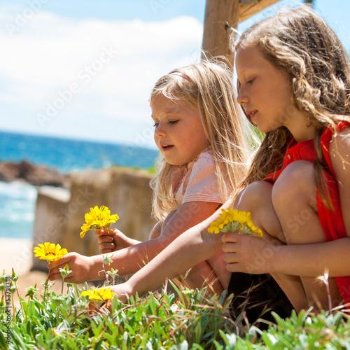 Two girls picking flowers.