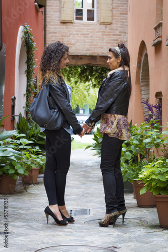 Young lesbian couple hand by hand in a old italian village