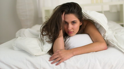 Sensual young Caucasian woman under bedsheets