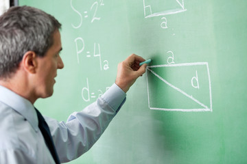 Male Professor Writing On Greenboard