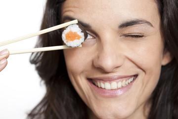 Frau mit Sushi auf Stäbchen