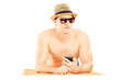 Guy with hat and sunglasses lying on a towel and listening music