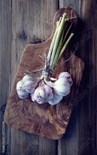 Garlic bulbs on wooden chopping board