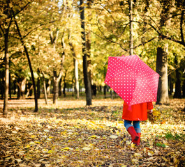 Little girl with polka dots umbrella walking through alley