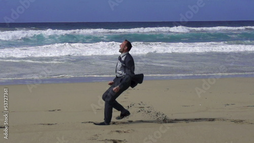 Businessman jumping on the beach, slow motion shot at 480fps