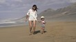Mother with his son having fun on the beach, slow motion shot at