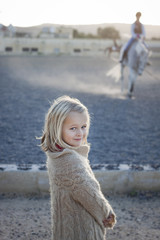 Girl watching a riding lesson