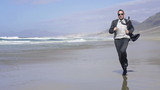 Young businessman jogging on the beach, slow motion shot at 240f