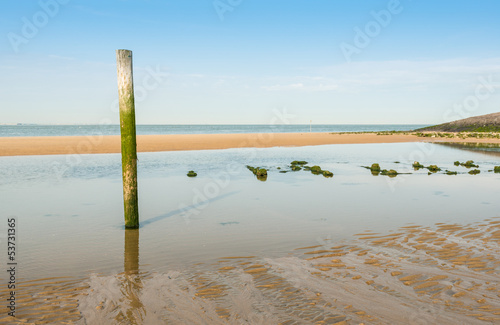 Tilted wooden pole on the beach