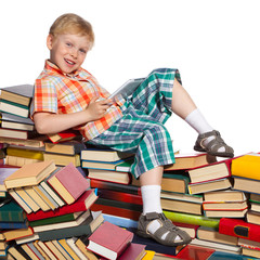 Little boy on a pile of books with tablet computer in his hand
