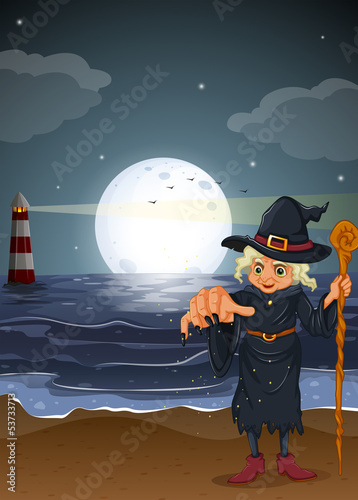 An old witch holding a stick at the beach