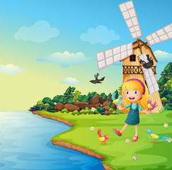 A girl playing with her birds near the barnhouse with windmill