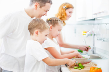 Happy family cooking salad