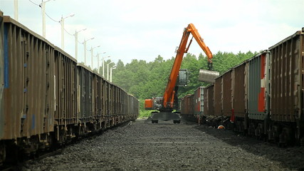 excavators, unloading coal from a cargo train.
