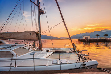 Sailing boats in marina at sunset.
