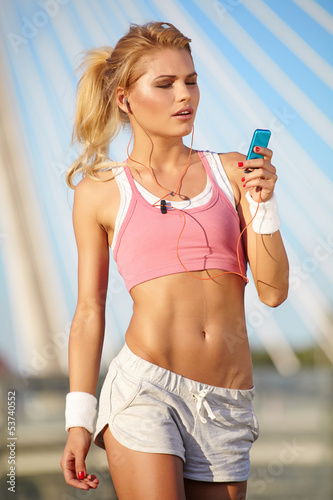 Stunning young blonde woman in pink sports bra rests and adjusti