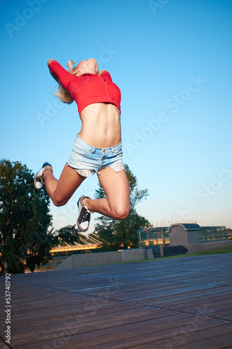 Athlete celebrating jumping and leaping against a night city.