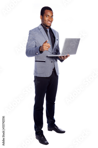 Smiling business man holding a laptop - isolated over a white ba