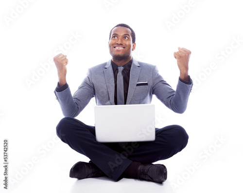 Successful business man with laptop and raised arms - isolated o