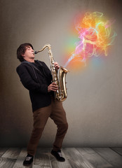 Attractive musician playing on saxophone with colorful abstract