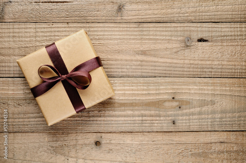Vintage gift box with bow on wooden background - 53744334
