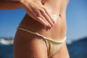 Woman puting suntan lotion on the beach