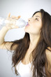 Young woman with amazing hair drinking water