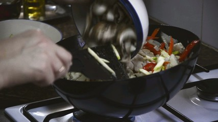 Adding mushrooms to frying chicken with vegetables and stir all