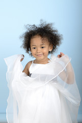little girl playing with the layers of her dress