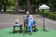 man sitting in a park on chair with table and lamp