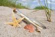 Flaschenpost mit Muschel, Seestern im Sand