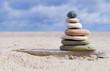Steinpyramide aus Holz mit Sandstrand