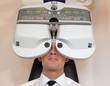 Постер, плакат: Customer of a optometrist or optician looking through phoropter