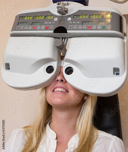 Customer of a optometrist or optician looking through phoropter