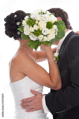 Kuss - Brautpaar isoliert küsst sich vor dem Brautstrauß