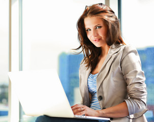 Happy businesswoman working on laptop