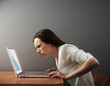 woman looking at laptop with distrust