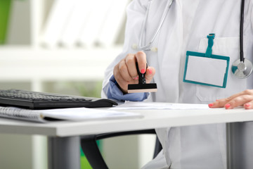 a doctor putting stamp on a document