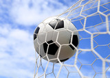 soccer ball in net on blue sky