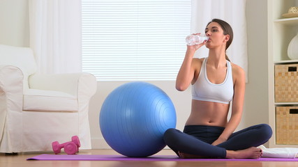 Healthy woman drinking water in work out clothes