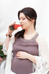 young pregnant woman drinks juice