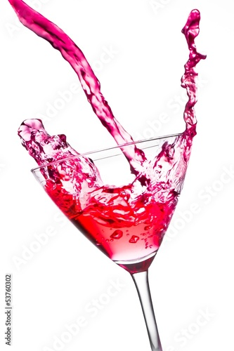 red cocktail with splashing in the tilted glass